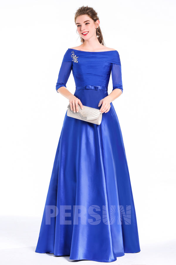 robe de soirée bleue col bateau ornée de bijoux à l'épaule gauche avec un sac